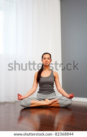young pretty woman doing yoga in room - stock photo