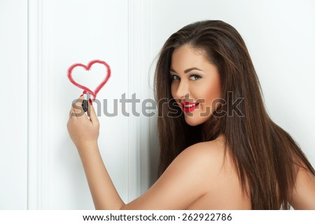 Young pretty woman drawing heart sign symbol on the wall with red lipstick. Beauty shot. Studio. - stock photo