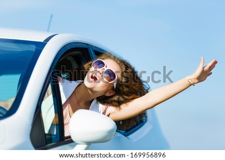 Young pretty woman driving car and leaning out of car window - stock photo