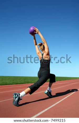 Young pretty woman exercising on a racetrack - stock photo