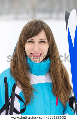 Young pretty woman going to skiing. Caucasian smiling girl with ski at winter outdoor activity - stock photo