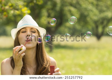 Young pretty woman have fun with soap-bubbles in summer park. Caucasian hipster girl in hat flow out bubbles  - stock photo