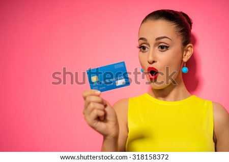 Young pretty woman holding plastic bank card. Young smiling lady showing blank business card. Pink background. - stock photo