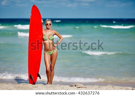 Young pretty woman holding surfboard on seaside beach - full length