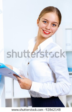 Young pretty woman in business wear working in office - stock photo