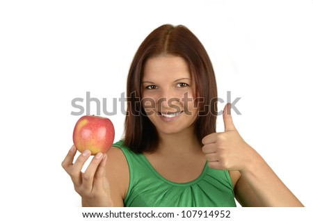 Young pretty woman in green top holding apple, smiling, while she holds her thumb up, portrait, Isolated