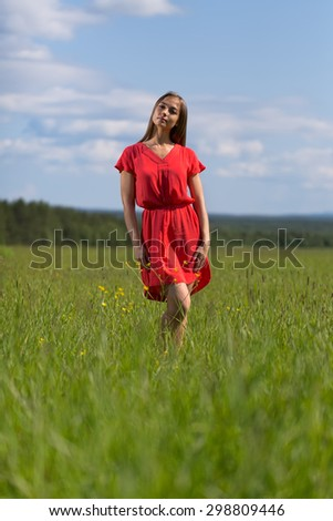 Young pretty woman in red dress against blue sky. - stock photo