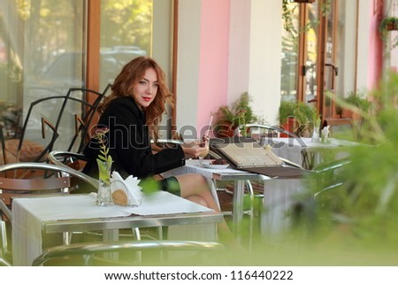 Young pretty woman in street cafe