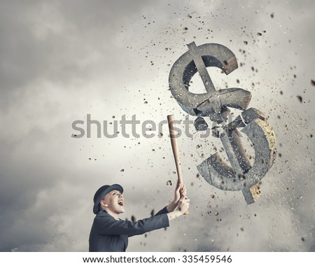 Young pretty woman in suit and hat crashing dollar sign with baseball bat - stock photo
