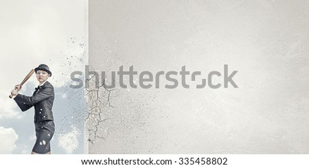 Young pretty woman in suit and hat crashing wall with baseball bat - stock photo