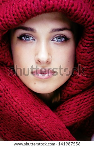 young pretty woman in sweater and scarf all over her face - stock photo