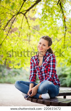 Young pretty woman in the park sitting on the bench
