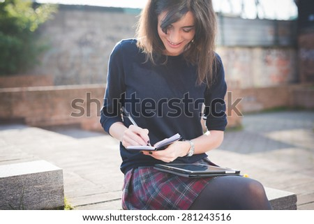 young pretty woman in town using tablet multitasking - stock photo