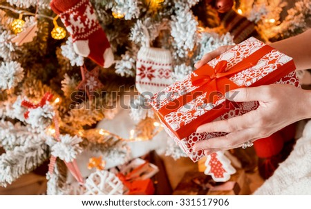 Young pretty woman in warm cozy clothes is sitting on the floor in her bright house near the christmas tree and holds gift box in her hands. - stock photo