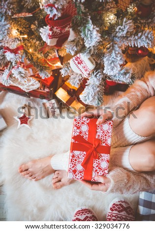 Young pretty woman in warm cozy clothes is sitting on the light wooden floor in her bright house near the christmas tree and holds gift box in her hands. - stock photo