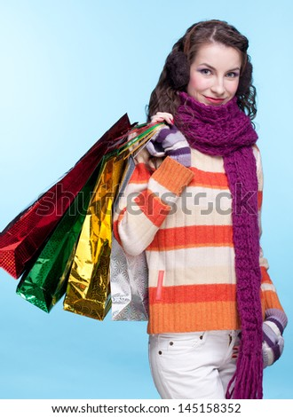 Young pretty woman in winter dress on blue background with shopping bags - stock photo