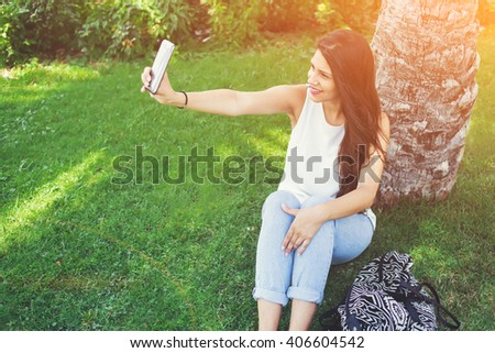 Young pretty woman is posing while photographing herself on cellphone for social network picture during recreation time in park, charming latin female is making self portrait with mobile phone camera - stock photo