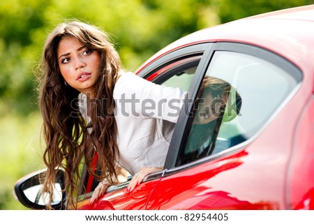 Young pretty woman looking at back of car - stock photo