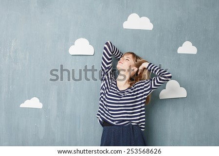 Young pretty woman  looking up over blue background with white paper clouds. The hands are touching the hair - stock photo