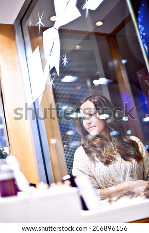 Young pretty woman looks at display through the glass in jewelry store
