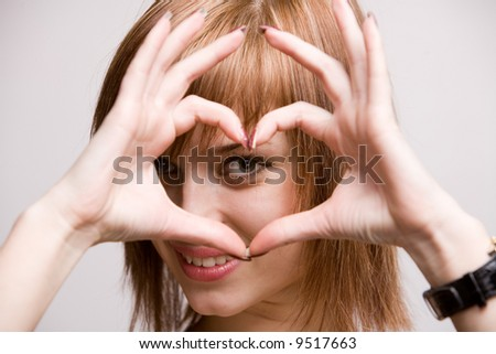 Young pretty woman making a heart shape