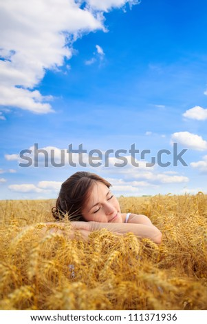 Young pretty woman on yellow wheat field