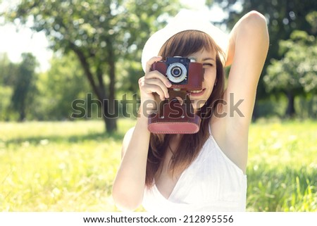 Young pretty woman posing with old film camera in summer park. Girl in White hat photograph with manual camera - stock photo