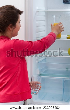 Young pretty woman reaching for orange juice in the fridge