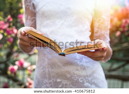 Young pretty woman reading a book and enjoy in beautiful park near flowers - stock photo