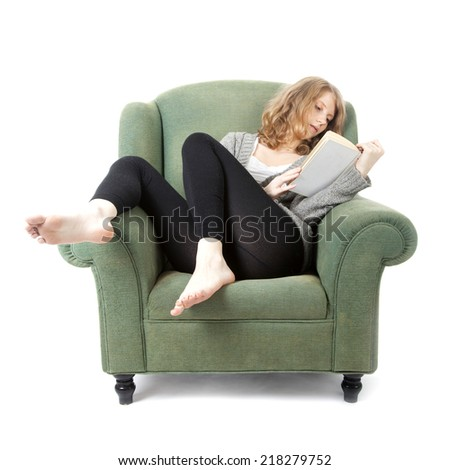 young pretty woman reading a book in armchair against white background