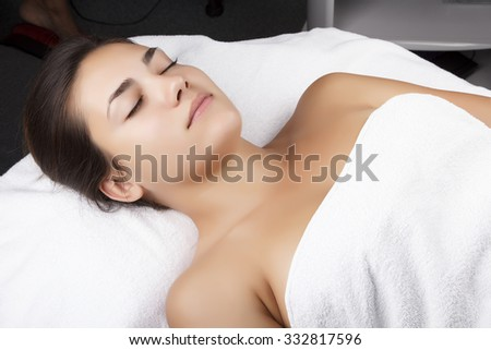 Young pretty woman receiving treatments in beauty salons. Young beautiful dark-haired woman in the office beautician lying on the couch. - stock photo