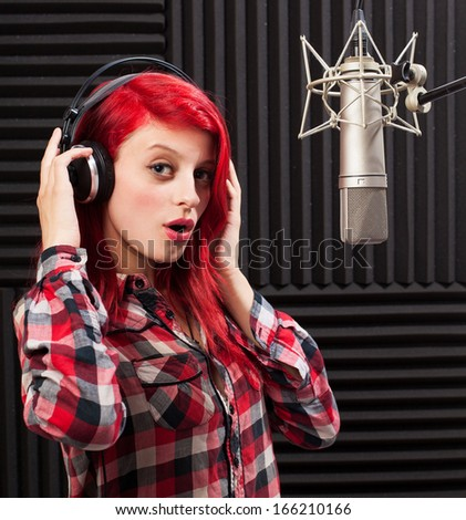 young pretty woman recording on audio studio - stock photo