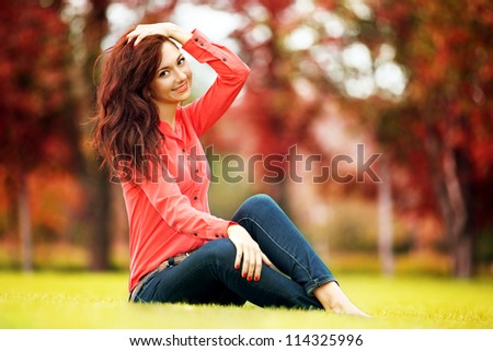 Young pretty woman resting in the autumn park - stock photo