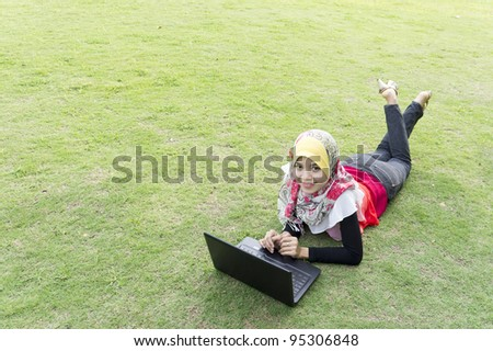 young pretty woman resting on green grass at summer park using laptop - stock photo