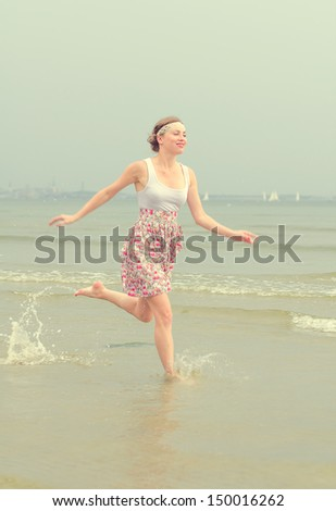 Young pretty woman running in the sea