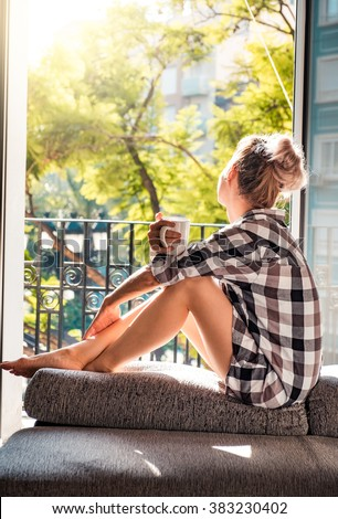 Young pretty woman  sitting at opened window drinking coffee and looking outside enjoys of rest - stock photo