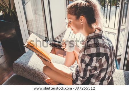 Young pretty woman  sitting at opened window drinking coffee and reading a book enjoys of rest - stock photo