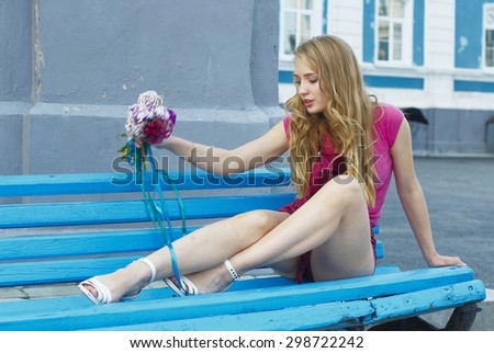 Young pretty woman sitting near entrance of house - stock photo