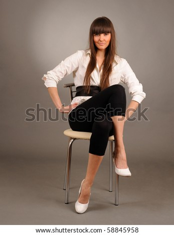 Young pretty woman sitting on a chair against gray background, studio shot. - stock photo