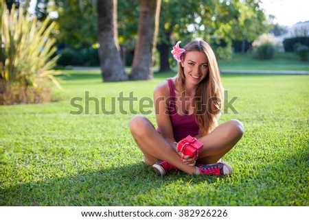 Young pretty woman sitting on a grass with gift box - stock photo