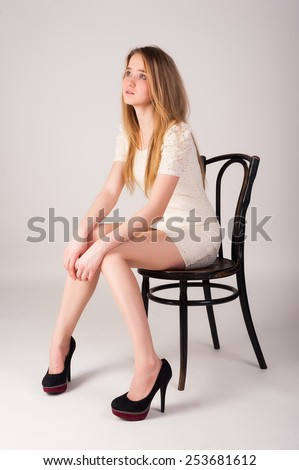 Young pretty woman sitting on chair at white background - stock photo