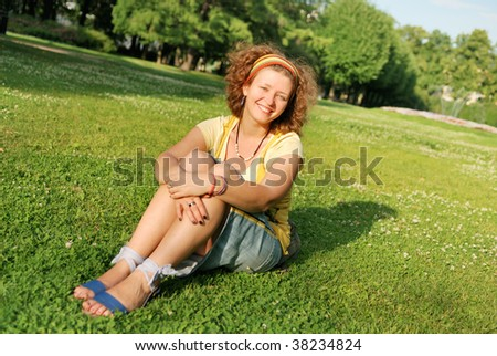 Young pretty woman sitting on grass and smiling - stock photo