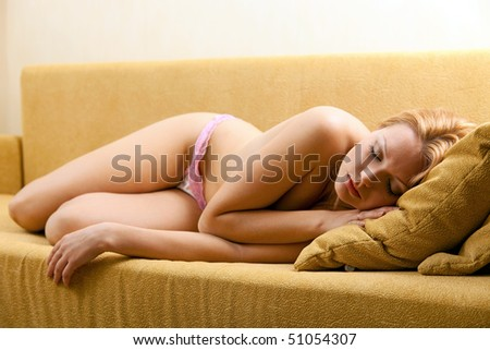 Young pretty woman sleeping on couch - stock photo