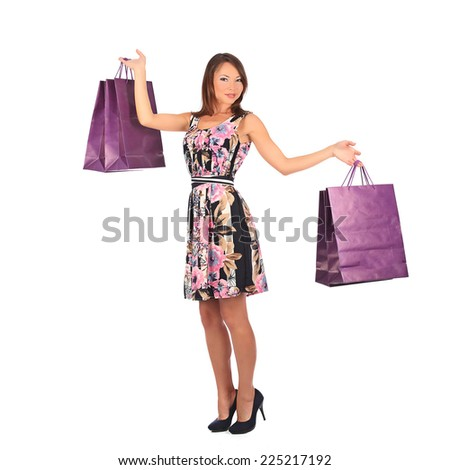 young pretty woman standing with color-full shopping bags, studio