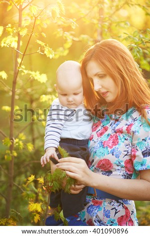 Young pretty woman stands on a background of the forest, holding a child. Woman and child looking at the leaves