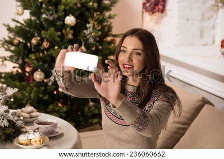 Young pretty woman taking selfie at home while sitting on sofa near Christmas tree - stock photo
