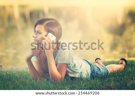 Young pretty woman talking on mobile phone - stock photo