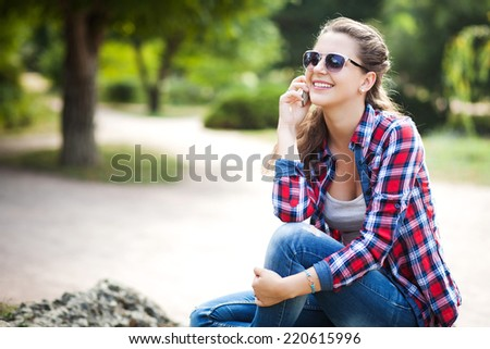 Young pretty woman talking on mobile phone profile, in autumn park. - stock photo