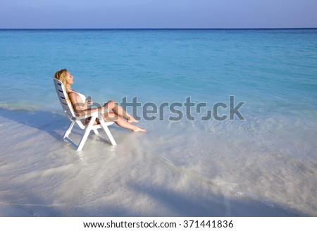 Young pretty woman tans in beach chair in sea - stock photo