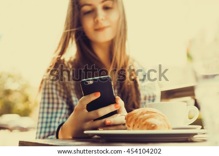 young pretty woman using laptop and smartphone in cafe, breakfast, launch, branch, outdoor portrait, closeup fashion model, phone touch screen, hipster, smile happy face - stock photo